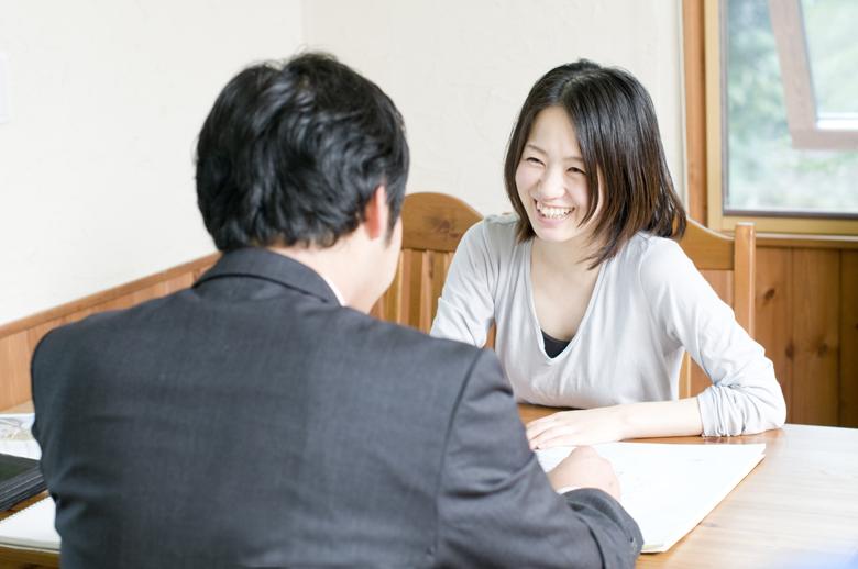 不動産会社に家の査定依頼をする女性