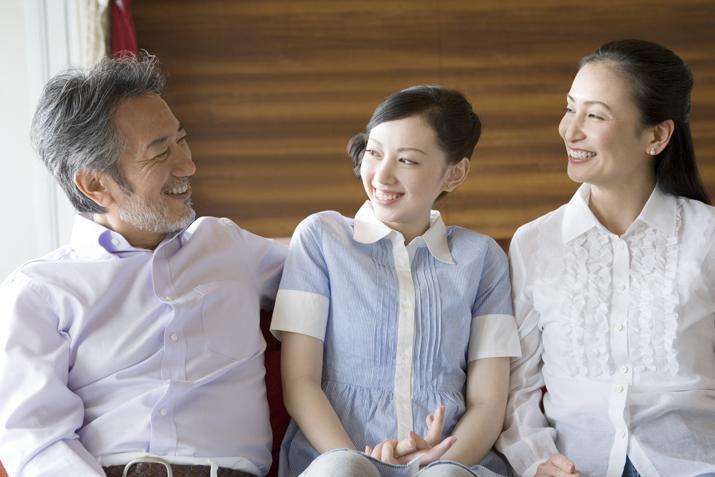 住み替え先のマンションで笑顔の老夫婦と娘